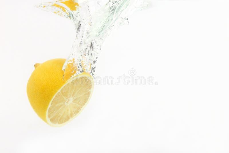 Gotas de limón del agua en el fondo blanco imagen de archivo