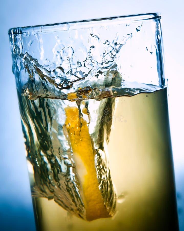 Gotas de limón en un vidrio de la bebida imagen de archivo
