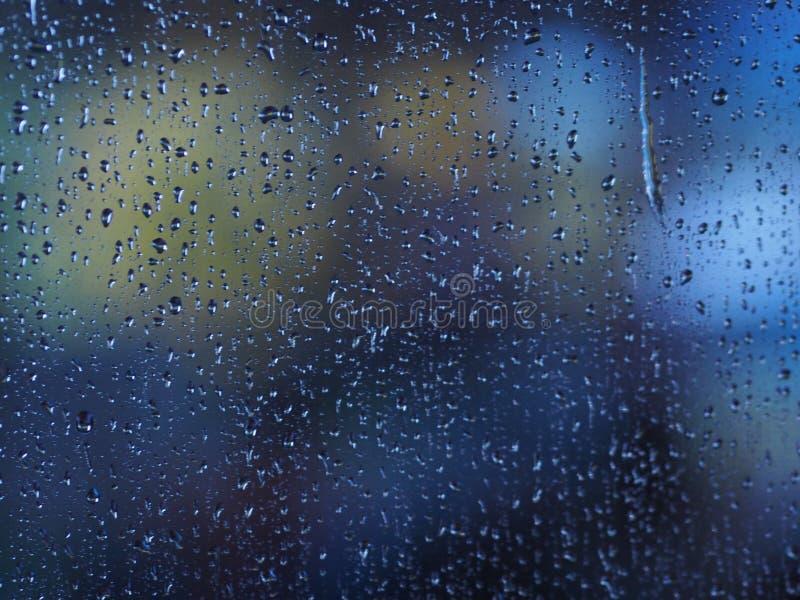 Gotas de lluvia en la foto del vidrio de la ventana en el movimiento azul del movimiento del agua del color del efecto del coche foto de archivo