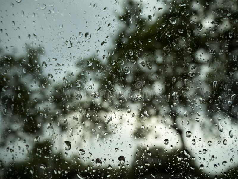 Gotas de lluvia en una ventanilla del coche en la tarde foto de archivo