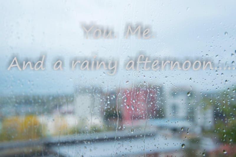 Gotas de lluvia en ventana y mandarle un SMS ' Yo Y concepto amoroso blando de una tarde lluviosa 'en días del mún tiempo imagen de archivo