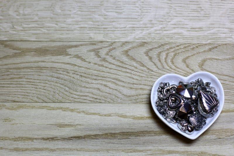 Gotas de los corazones del metal en fondo de madera fotos de archivo libres de regalías