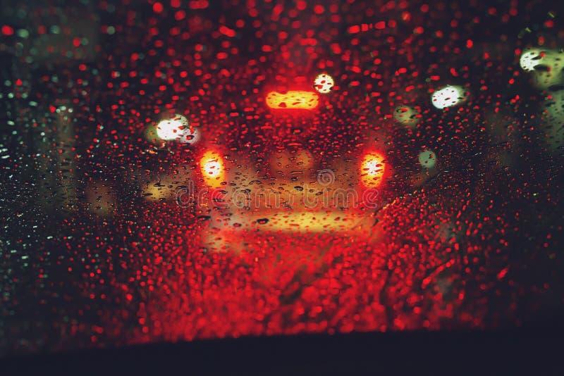 Gotas do chuvisco da chuva no para-brisa de vidro na noite Rua na chuva pesada Luz da cauda de Bokeh Foco macio imagens de stock royalty free