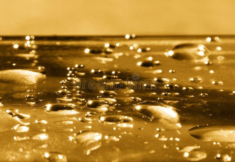 Gotas douradas da água imagem de stock royalty free