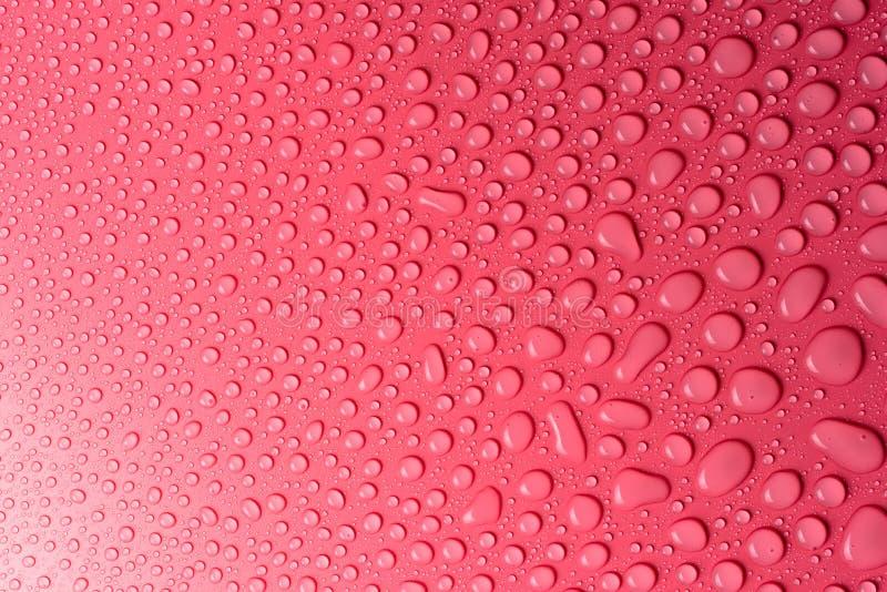 Gotas em um cor-de-rosa, fundo da água do resíduo metálico iluminado com uma luz delicada imagens de stock royalty free