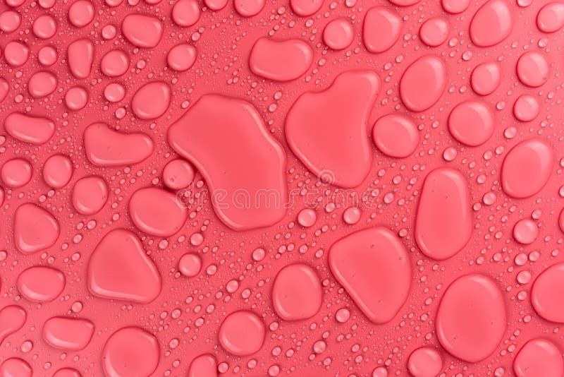 Gotas em um cor-de-rosa, fundo da água do resíduo metálico iluminado com uma luz delicada imagem de stock