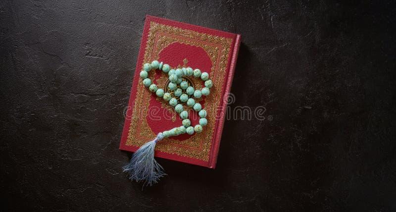 Gotas islámicas del quran y del rosario del libro sagrado en fondo negro de la textura de la piedra o de la pizarra Concepto islá imagen de archivo libre de regalías