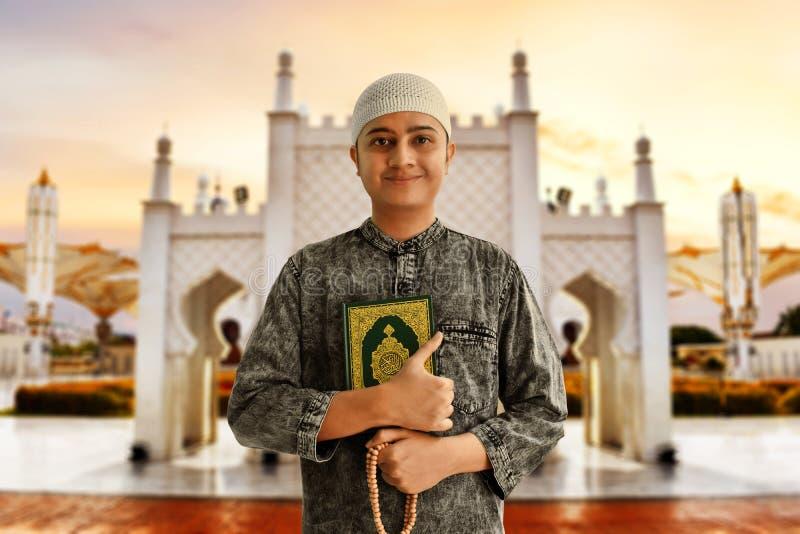 Gotas musulmanes asiáticas religiosas del quran y del rosario de la tenencia del hombre foto de archivo
