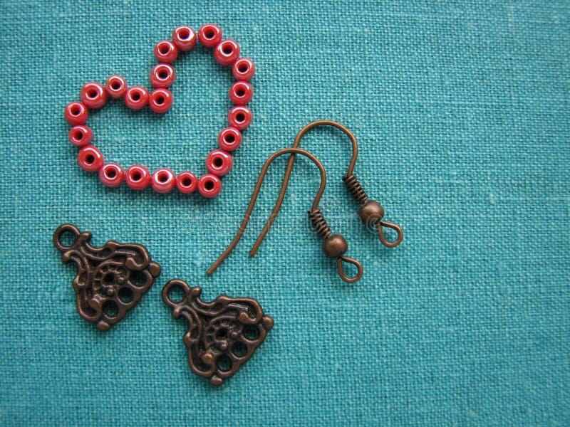 Gotas rojas en la forma de corazón, haciendo los pendientes, joyería hecha a mano imágenes de archivo libres de regalías