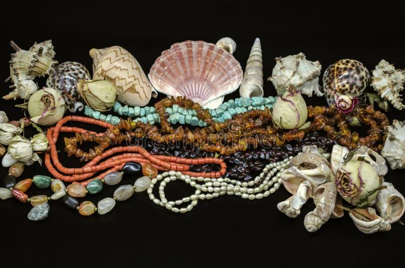 Gotas viejas de la turquesa, coral rojo, ámbar, piedra del granate, ágata multicolora, perlas entre diversas cáscaras en fondo ne foto de archivo libre de regalías