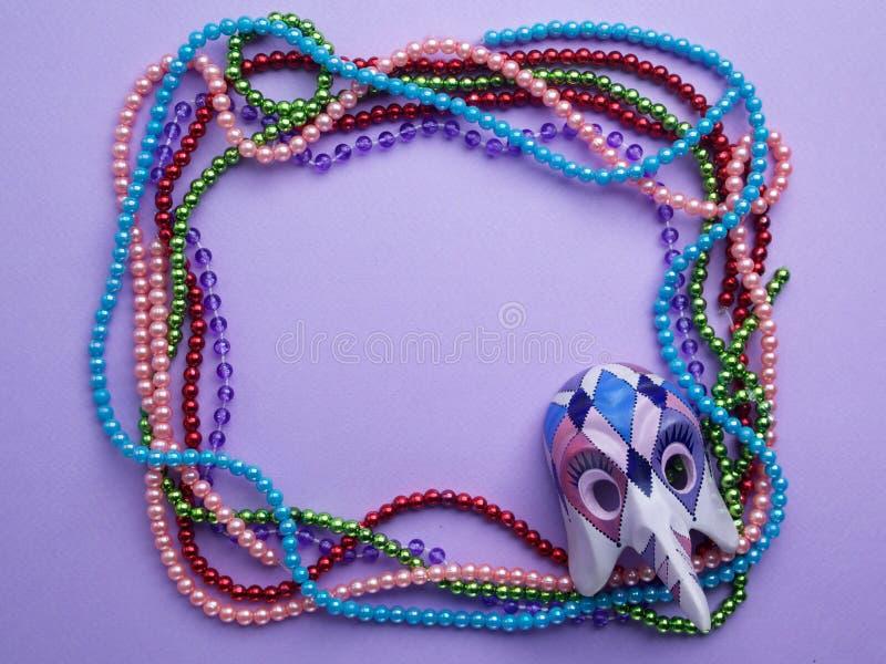 Gotas y máscara de Mardi Gras que hacen un marco con el espacio de la copia en fondo púrpura Endecha plana Visión superior foto de archivo