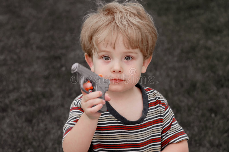 Gotcha. A young boy holding a water gun stock images
