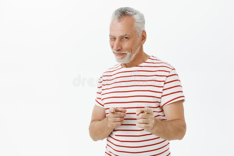 gotcha Portrait du retraité mûr masculin activé charismatique et optimiste dans le T-shirt rayé se dirigeant avec l'index photos stock