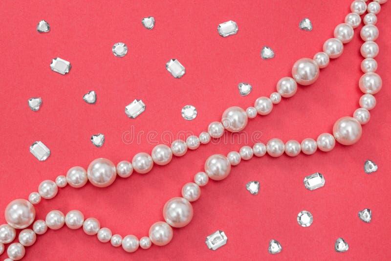 Gotee el collar y las gemas brillantes en fondo rosado fotografía de archivo