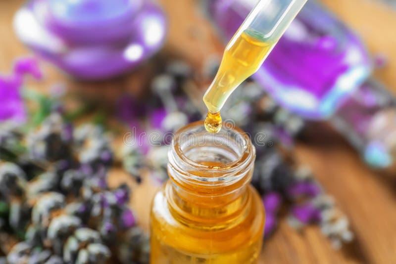 Gotejamento do óleo essencial da alfazema na garrafa, close up imagens de stock royalty free