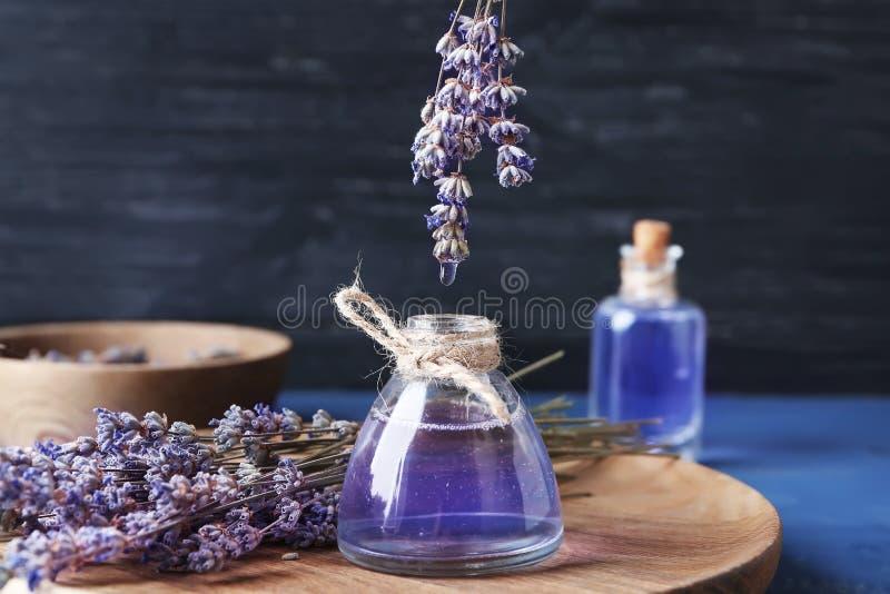 Gotejamento do óleo essencial da alfazema na garrafa na placa de madeira fotos de stock