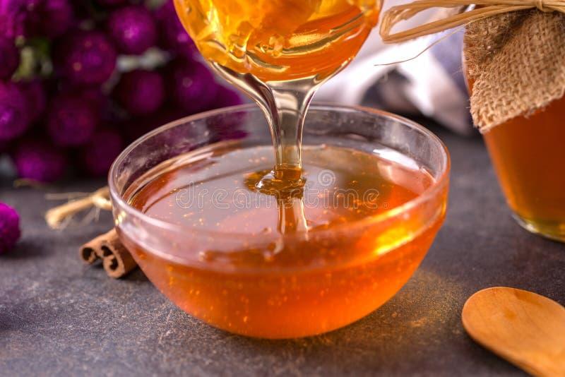 Gotejamento do mel na bacia de vidro no fim da tabela acima imagem de stock royalty free