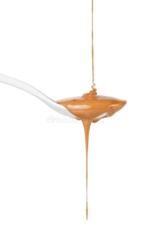 Gotejamento do molho do caramelo na colher fotografia de stock