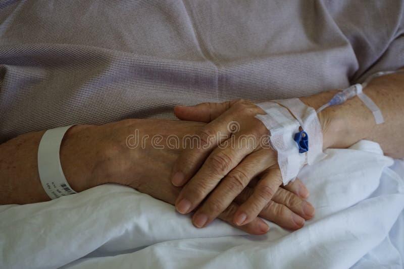 Gotejamento paciente da mão que recebe uma solução salina e um oxigenação na cama no hospital foto de stock royalty free