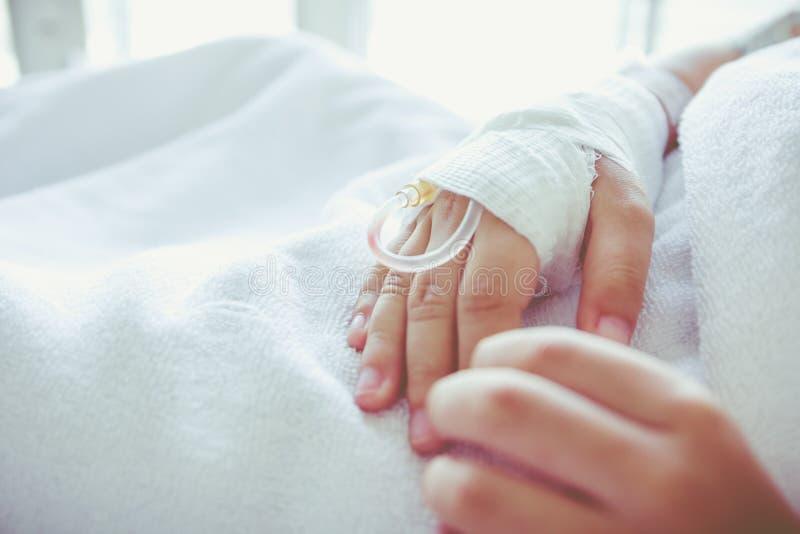 Gotejamento salino do intravenous (iv) na mão paciente de uma criança vintage foto de stock royalty free