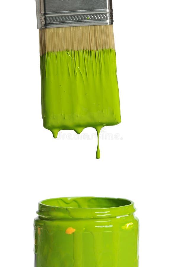 Gotejamento verde da pintura de uma escova fotografia de stock