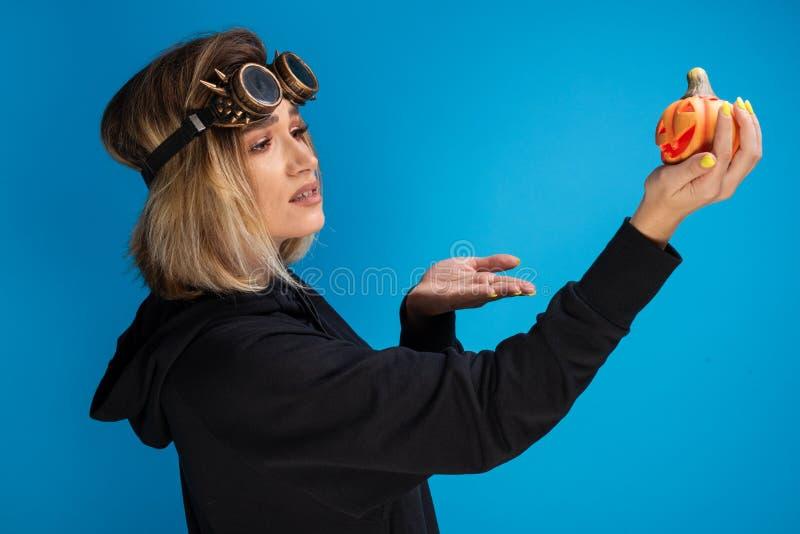 goth女孩佩带的蒸汽低劣的玻璃画象想知道在橙色被雕刻的南瓜的 免版税库存照片