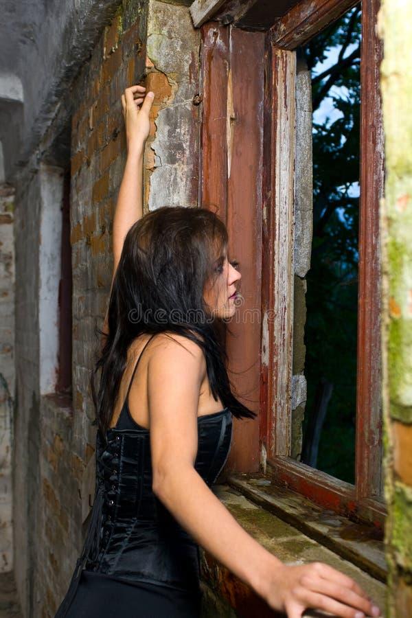 goth девушки смотря вне окно стоковая фотография