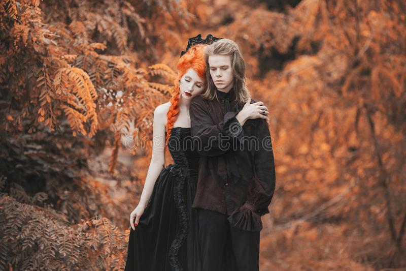 Goth couple in halloween costume. Gloomy vampire in baroque clothes. Redhead woman vampire in black baroque dress. Goth clothes fo stock images