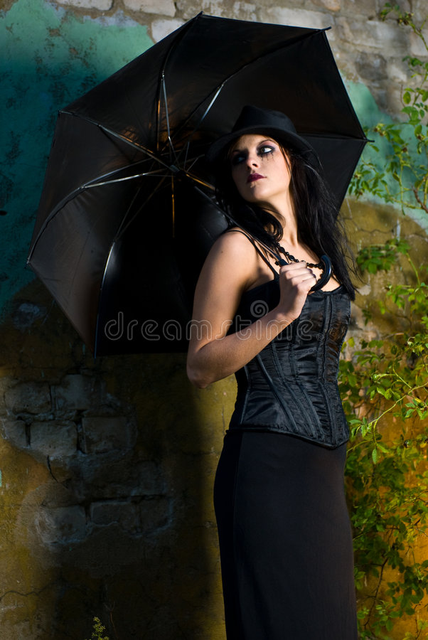 Goth Girl. A goth girl wearing a hardtop hat and holding an umbrella, standing against a ruined wall stock images