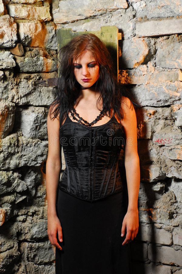 Goth Girl. A sad goth girl posing against a stone wall in ruined premises royalty free stock photos