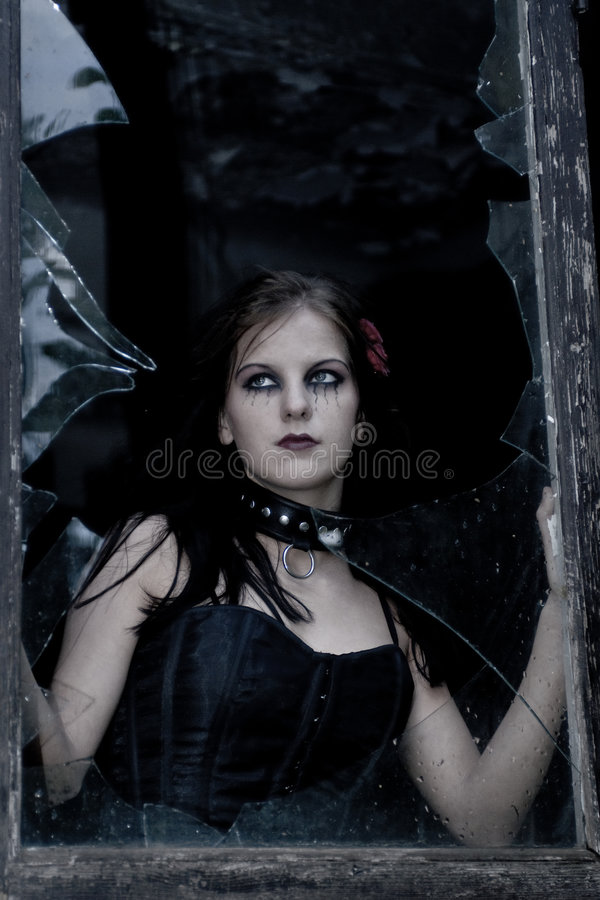 Goth girl and broken window royalty free stock images