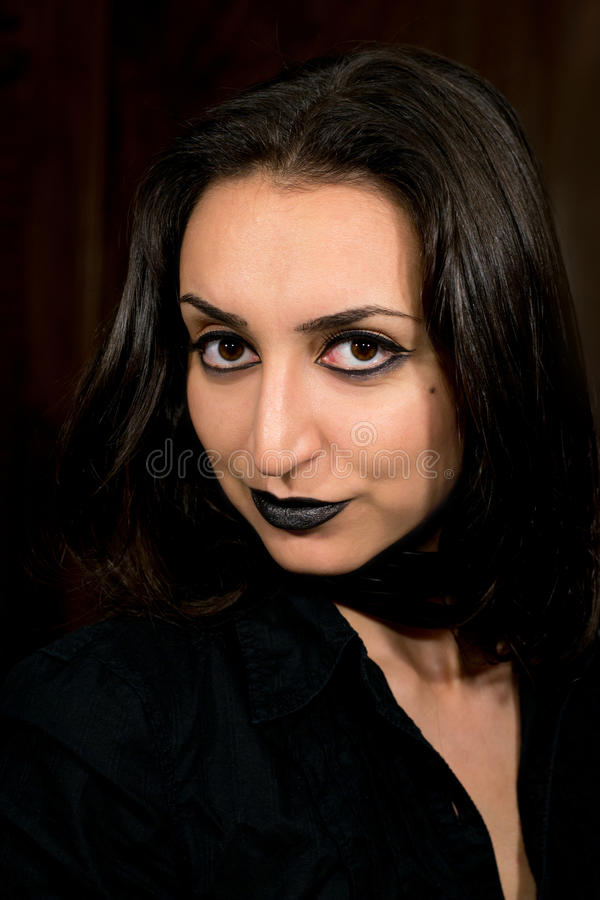Goth girl with dark hair and dark eyes smiling at the camera.  royalty free stock photography