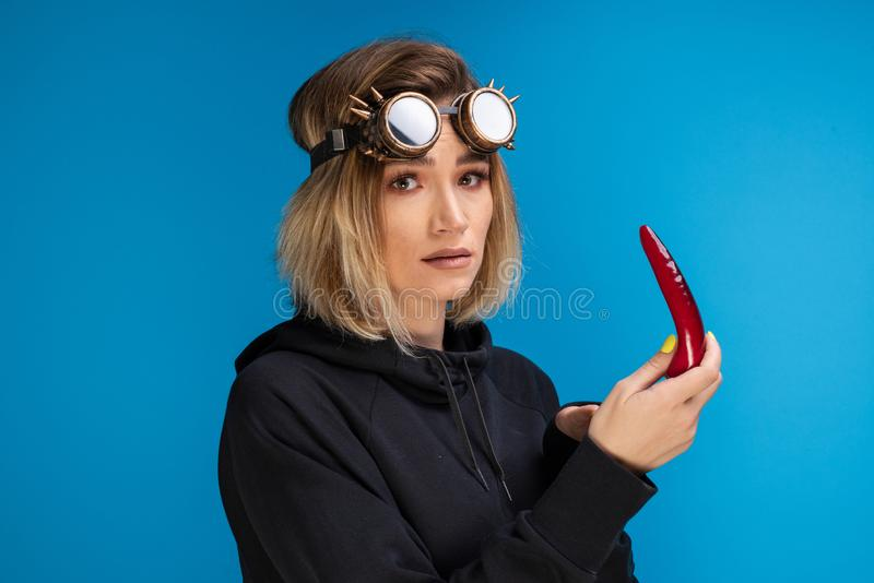 Goth girl wearing steam punk glasses and dark hoodie is looking confused at a red chilli pepper royalty free stock image