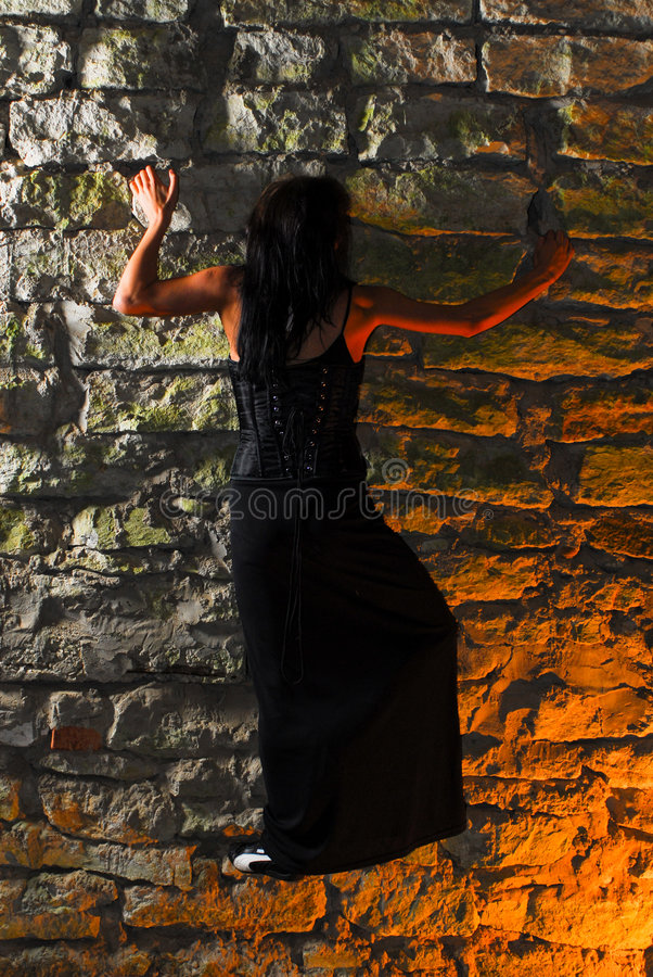 Goth woman climbing stone wall royalty free stock photography