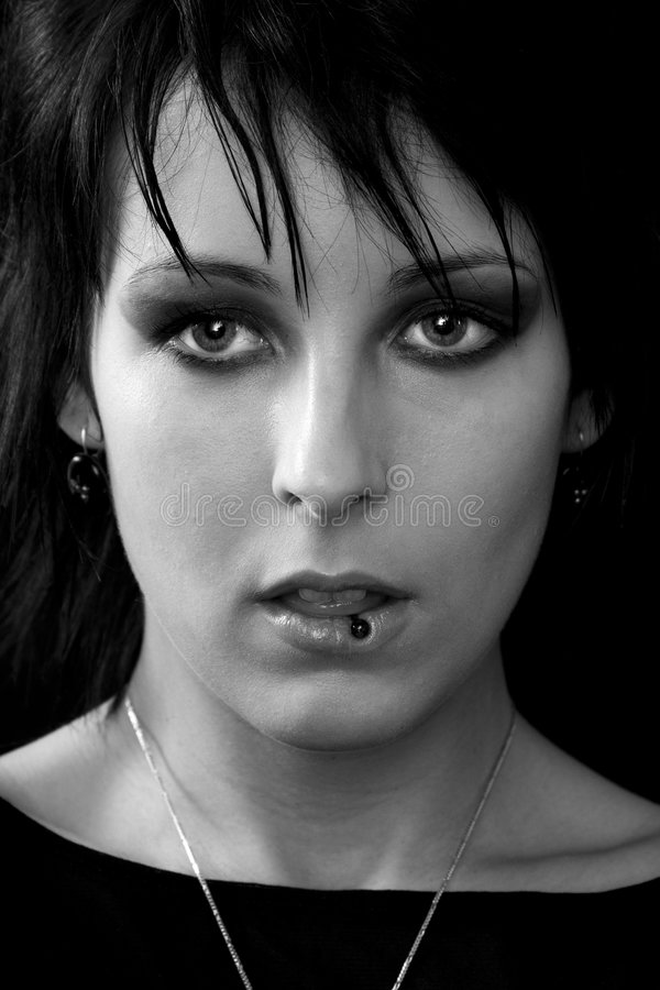 Goth woman tongue piercing. Portrait of an attractive young woman with goth-style make-up and tongue piercing stock photography