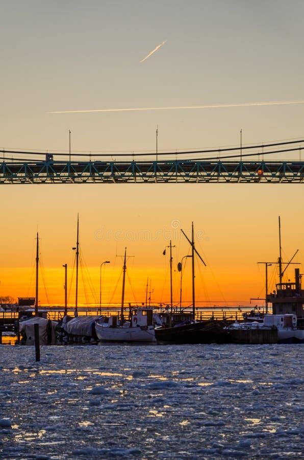 Gothenburg - por do sol sobre barcos da pesca e de navigação no rio congelado de Gota na ponte de Hisingsleden durante o inverno foto de stock royalty free