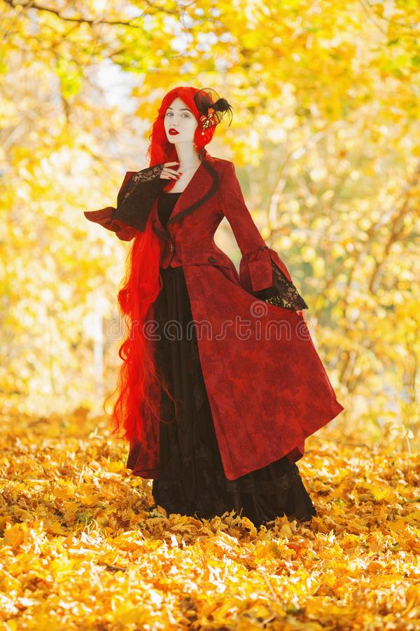 Gothic autumn coat. Fairy cosplay. Young fairy queen on autumn background. Vampire with pale skin. Fairy outfit for halloween. stock images