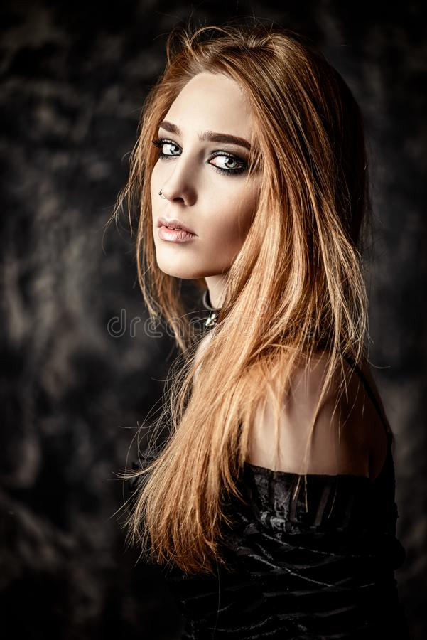 Gothic beautiful woman. Close-up portrait of a beautiful hipster woman with piercings in the nose over grunge background. Beauty, make-up. Fashion. Gothic style royalty free stock photography