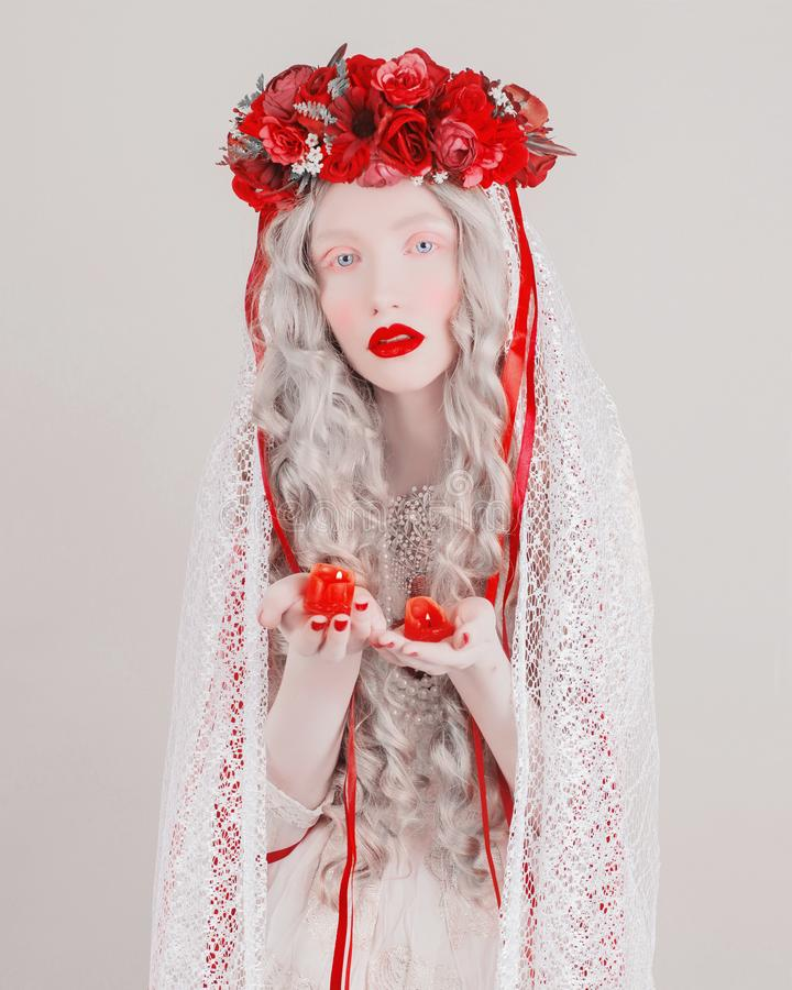 Gothic blonde woman vampire in flower wreath with pale skin and red lips. Mysterious creepy witch with long hair and candle. royalty free stock image
