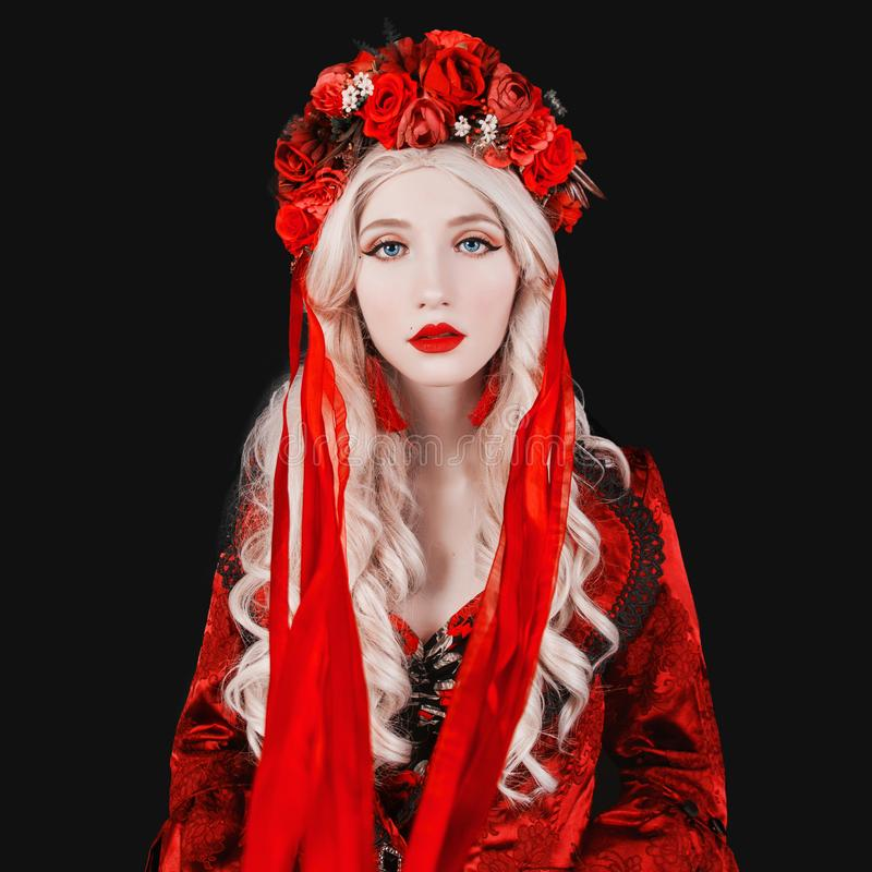 Gothic blonde woman vampire in flower wreath with pale skin and red lips. Renaissance vampire with long hair. Gothic witch in stock photo