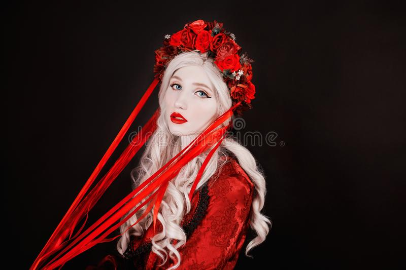 Gothic blonde woman vampire in flower wreath with pale skin and red lips. Renaissance vampire with long hair. Gothic witch in. Wreath with ribbons. Renaissance stock photos