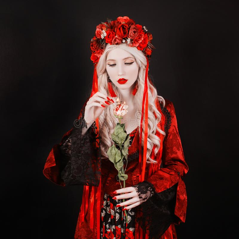 Gothic blonde woman vampire in flower wreath with pale skin and red lips. Rose in fire. Scary creepy vampire with long hair. Gothic witch in wreath with stock image