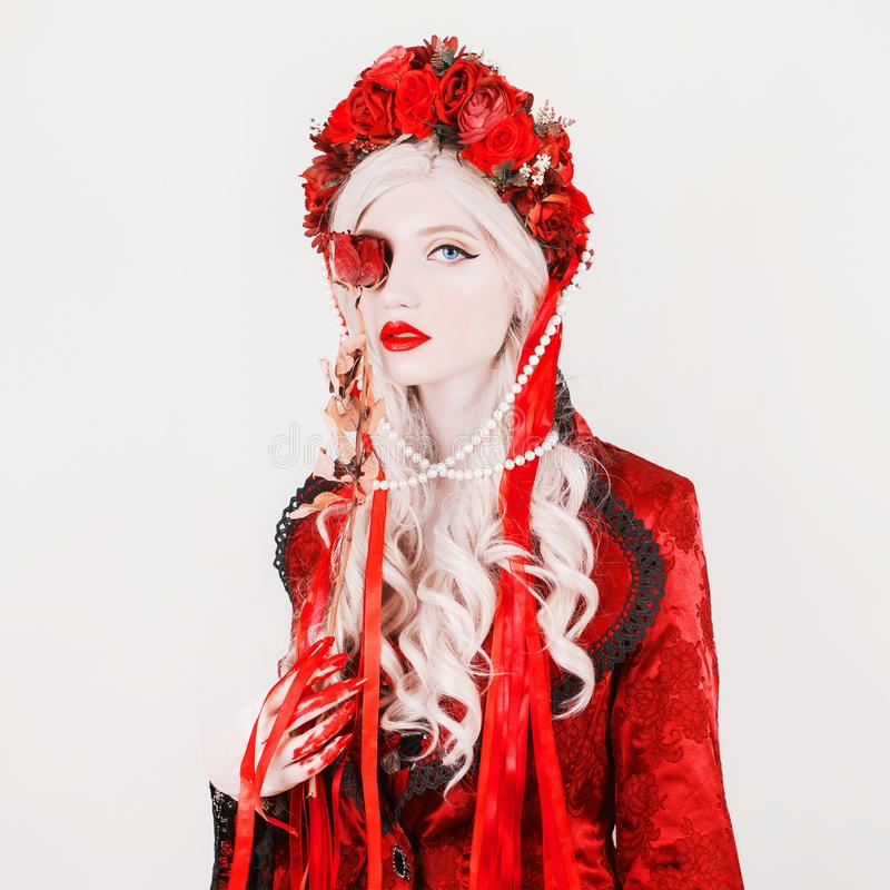 Gothic blonde woman vampire in flower wreath with pale skin and red lips. Vampire from nightmare with blood. Gothic witch in. Wreath with ribbons. Terrible royalty free stock image