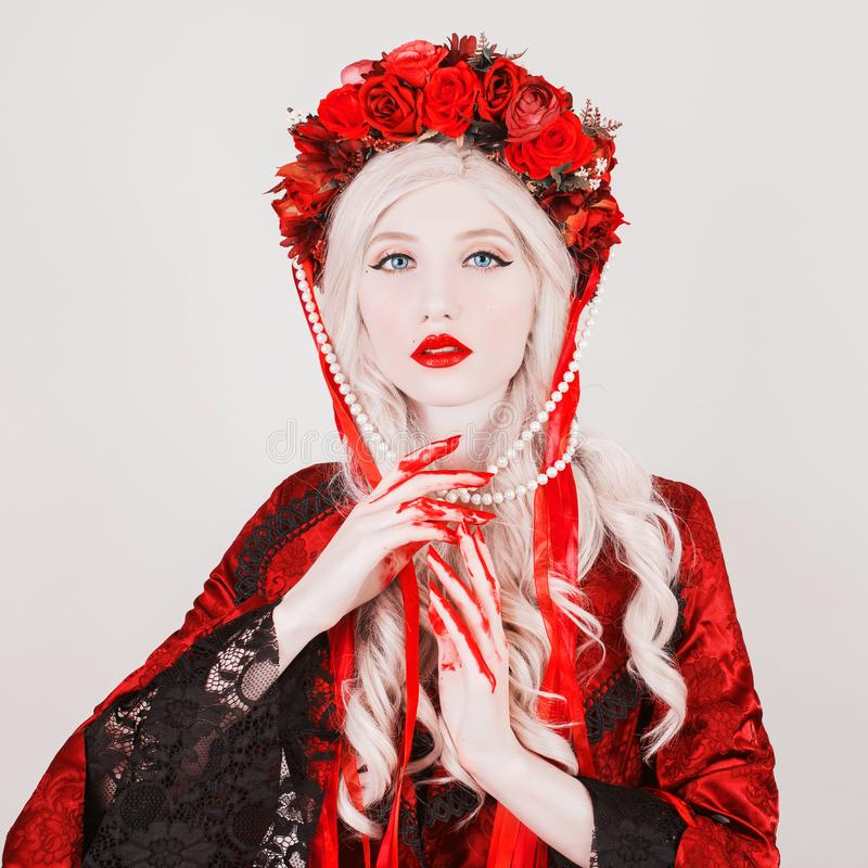Gothic blonde woman vampire in flower wreath with pale skin and red lips. Vampire from nightmare with blood. Gothic witch in. Wreath with ribbons. Terrible stock photos