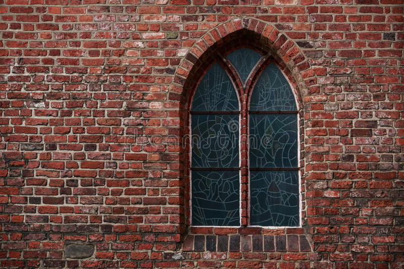 Gothic brick wall with a window. A stained glass window royalty free stock photography