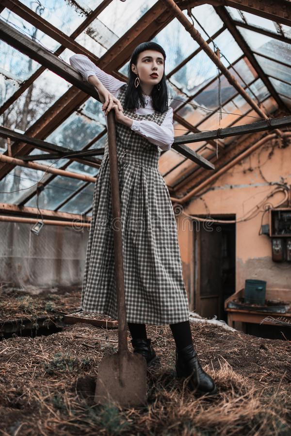 Gothic brunette model in dress keep shovel. Victorian fashion. Gothic model on grunge background. Mysterious brunette woman with. Bang. Model in dress on dark royalty free stock images