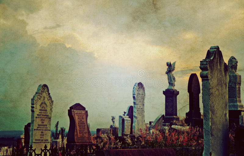Gothic cemetery landscape at twilight. With old headstones and angels under a dramatic, luminous sky. Vintage grunge textured image. Selective focus with copy royalty free stock image