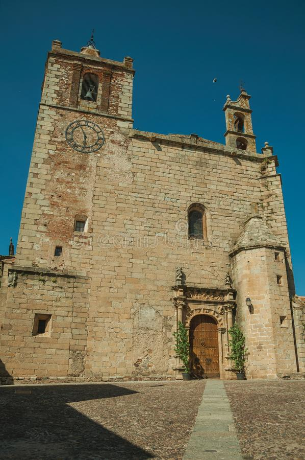 Gothic church facade with steeples and wooden door at Caceres stock image