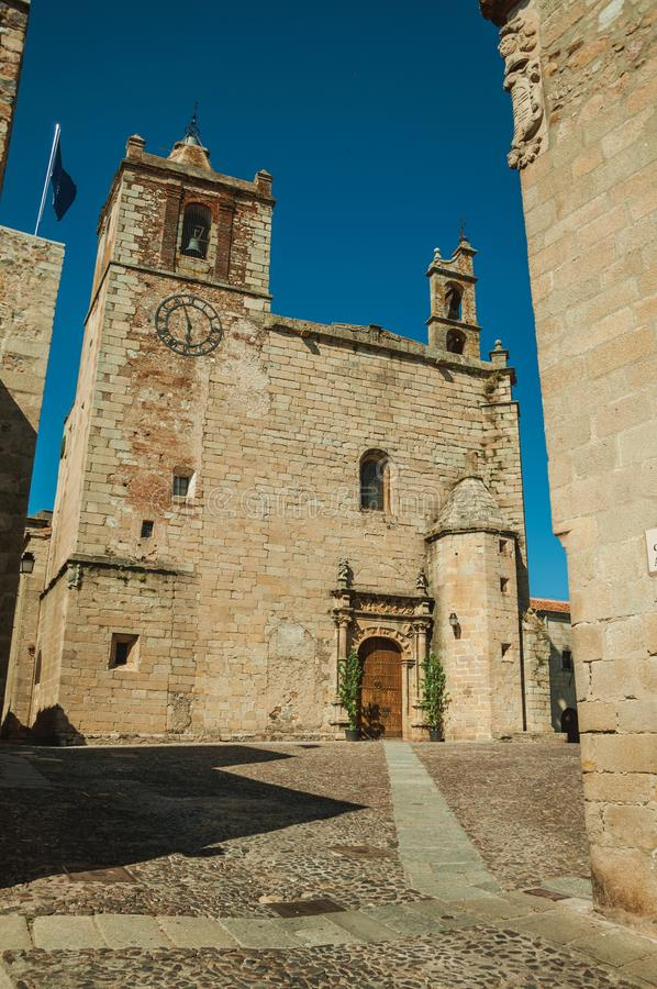 Gothic church facade with steeples and wooden door at Caceres stock photography