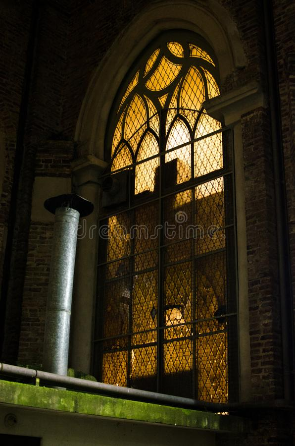 Gothic church window of 1900`s. At an historic location in Buenos Aires, part of it`s early century architecture, an illuminated gothic window in low key light royalty free stock images